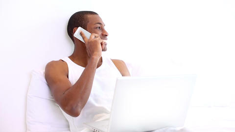 Happy man lying on bed phoning and using laptop Footage
