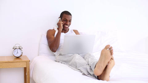 Handsome man lying on bed phoning and using laptop Footage