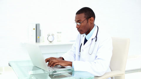 Concentrating Doctor Working On His Laptop stock footage