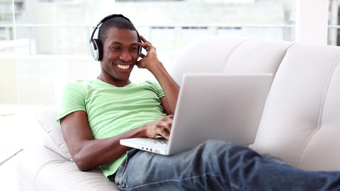 Smiling man lying on couch listening to music usin Footage