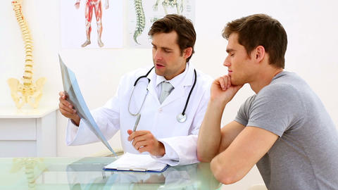 Earnest doctor discussing xray with his patient Footage