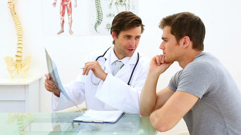 Handsome doctor discussing xray with his patient Footage