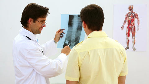 Doctor looking at xray with patient and smiling Footage