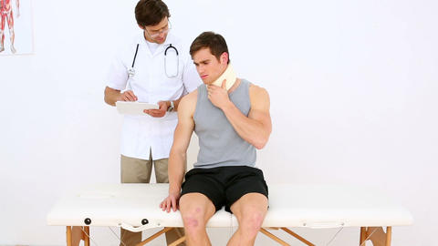 Physiotherapist talking to patient wearing a neck  Footage