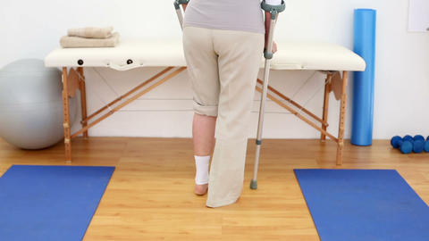Injured patient in crutches walking away from came Footage