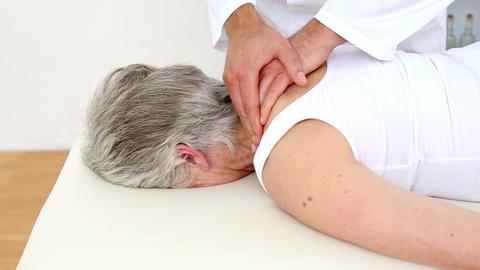 Doctor rubbing senior patients shoulders Footage
