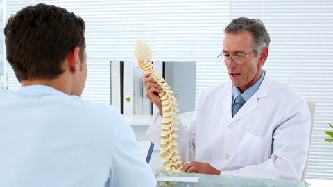 Mature doctor talking to his patient about spine m Footage
