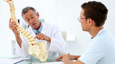 Mature doctor speaking to his patient about spine  Footage