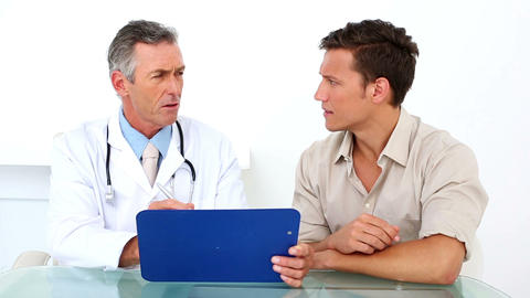 Patient listening to his doctor holding clipboard Footage