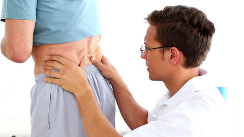 Physiotherapist rubbing mature patients lower back Footage
