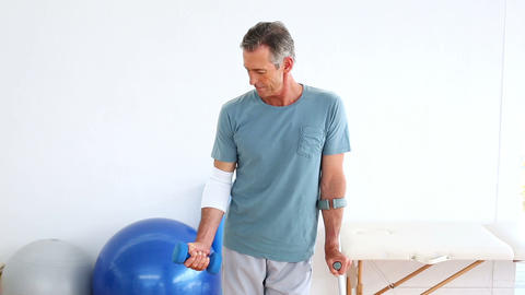 Injured patient on crutches lifting dumbbell Footage