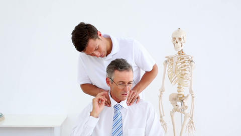 Physiotherapist giving businessman a shoulder rub Footage