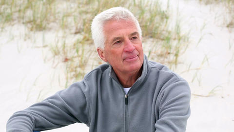 Retired white haired man relaxing on the beach Footage