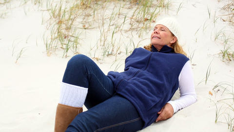 Happy retired woman relaxing on the beach Footage