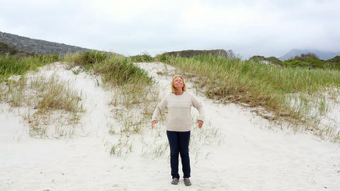 Happy retired woman standing on the beach Footage