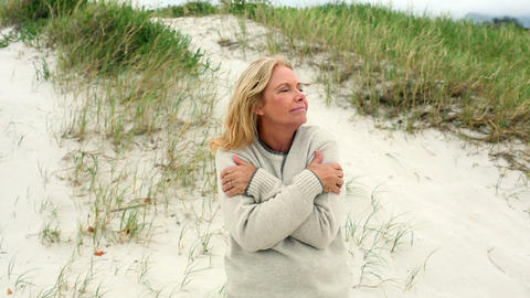 Smiling retired woman shivering on the beach Footage