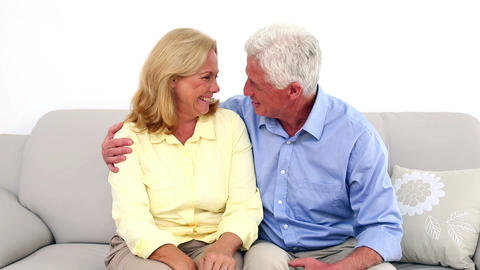 Smiling retired couple talking on the couch Footage