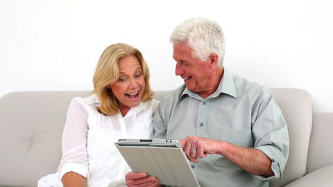 Retired Couple Using Their Tablet On The Couch stock footage