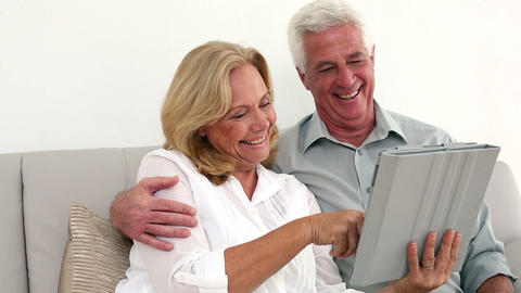 Retired happy couple using their tablet on the cou Footage