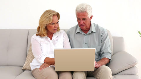 Retired happy couple using their laptop on the cou Footage