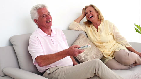 Retired smiling couple watching television on the  Footage