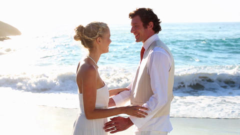 Newlyweds laughing and looking out to the sea Footage