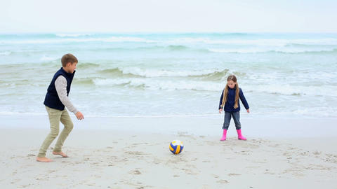 Siblings playing football on the beach Footage
