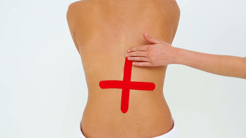 Woman having red kinesio tape applied to back Footage