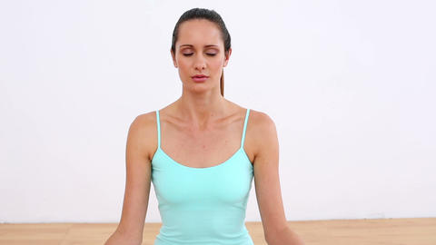 Fit model sitting in lotus pose smiling at camera Footage