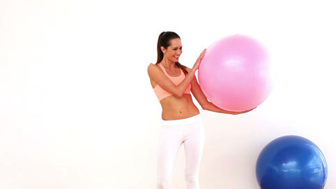 Fit model holding exercise ball and smiling at cam Footage