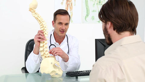 Doctor Showing His Patient A Model Of A Spine stock footage
