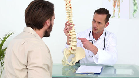 Doctor showing his patient a skeleton spine model Footage
