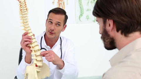 Doctor showing his patient a spine model Footage