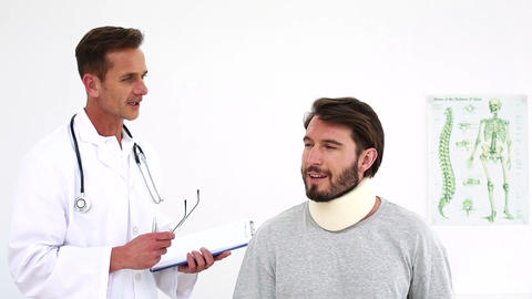 Doctor checking on injured patient in a neck brace Footage
