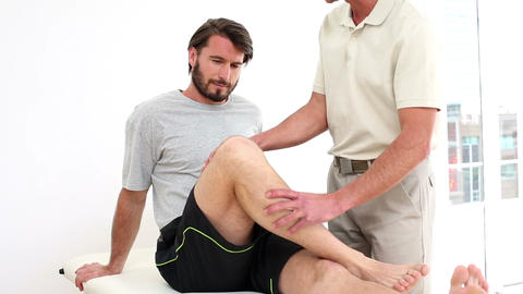 Physical therapist checking injured patients knee Footage