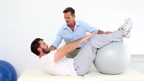 Physical therapist helping his patient do a sit up Footage