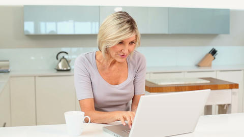 Blonde woman drinking coffee using her laptop Footage