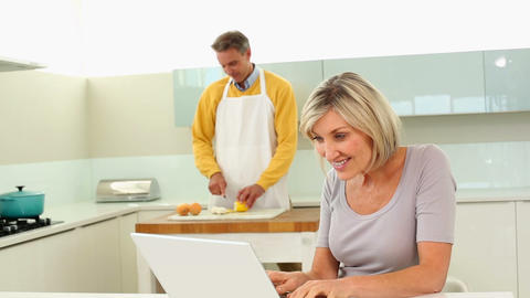 Woman using laptop while her husband is slicing ve Footage