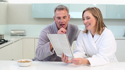 Mature smiling couple doing the crossword puzzle a Footage