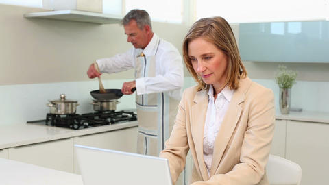 Businesswoman using laptop while husband cooks din Footage