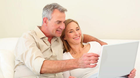 Mature couple using laptop together on the couch Footage