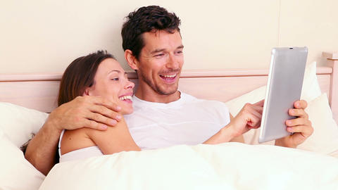 Couple lying in bed using digital tablet Footage