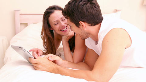Happy couple lying on bed using tablet Footage