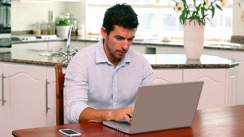 Handsome man using laptop at the table Footage