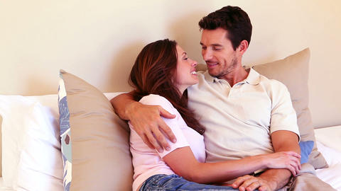 Happy couple cuddling on bed and chatting Footage
