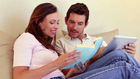 Happy couple sitting on sofa using tablet pc toget Footage