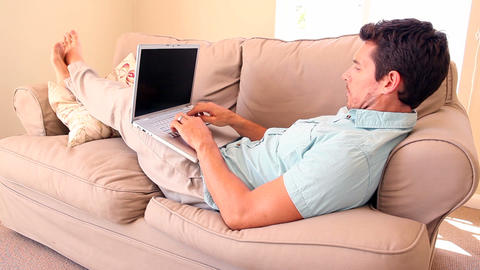Man lying on couch typing on laptop Footage