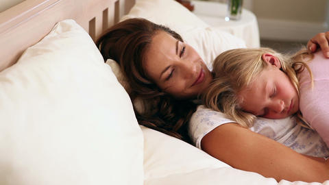 Mother and daughter sleeping together in bed Footage