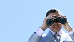 Young businessman looking through binoculars Footage