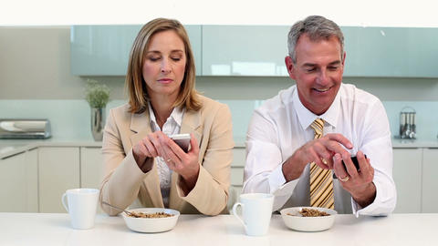 Couple having breakfast and texting before work Footage